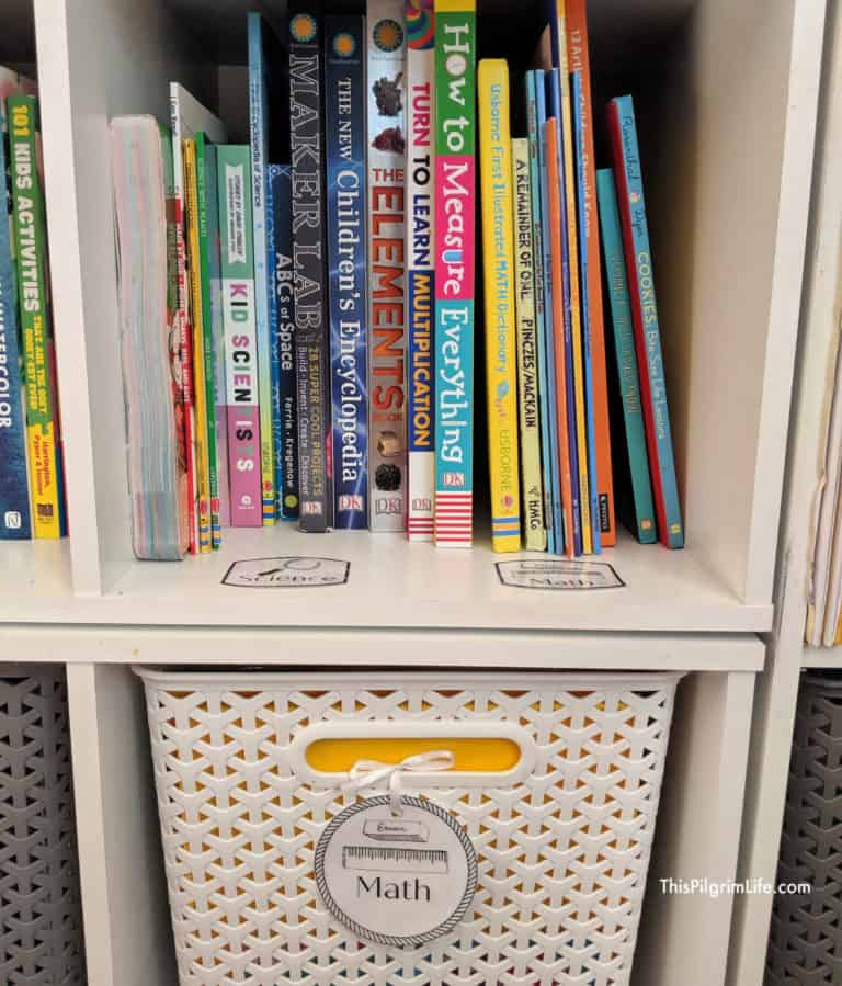 "Organzing homeschool books by subject with white cubbies that have subject picture labels on them, basket underneath cubby filled with books that is white and labeled with ""math"""