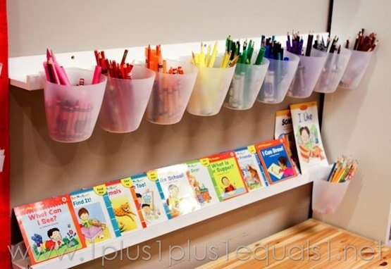 Homeschooling supplies that are organized in a mounted white storage system. Colorful art supplies in each cup. Shelf underneath supplies with books