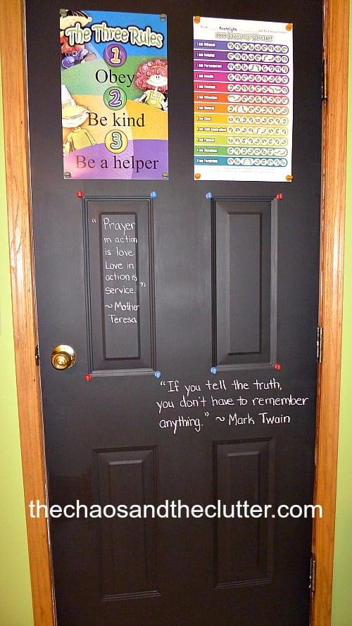 Homeschool organization hack showing a painted black door with chalboard paint, chalk writing is on the door and learning posters are mounted to the door. The door has a gold handle and wood framing.