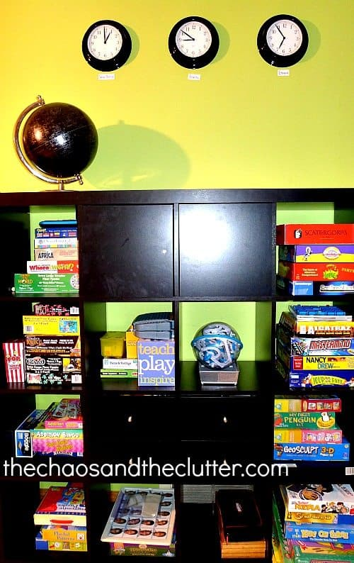 Green wall with three black clocks, huge shelving unit that is black storing stacked homeschool games, black globe on to top of storage