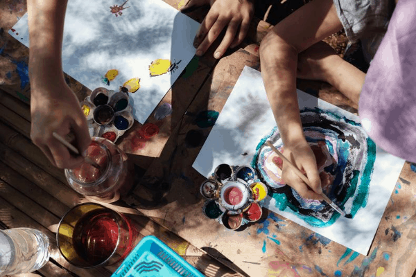 homeschooling children doing an art project outside. shot from overhead of just there arms painting using a variety of colors