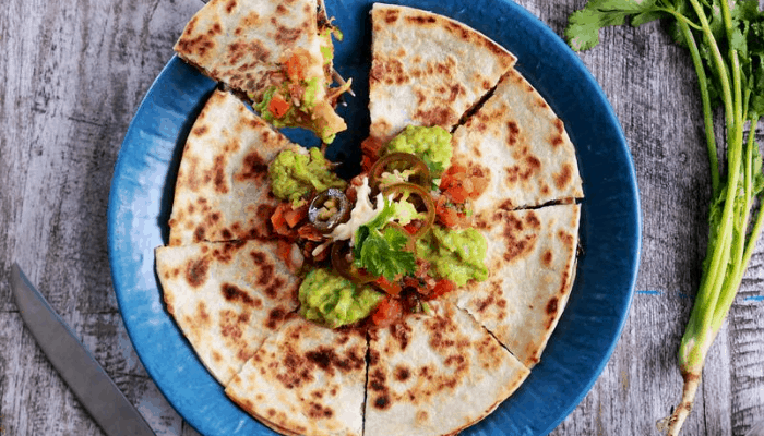 Quesadilla topped with salsa, guacamole, and jalapenos on a blue plate and wood background.