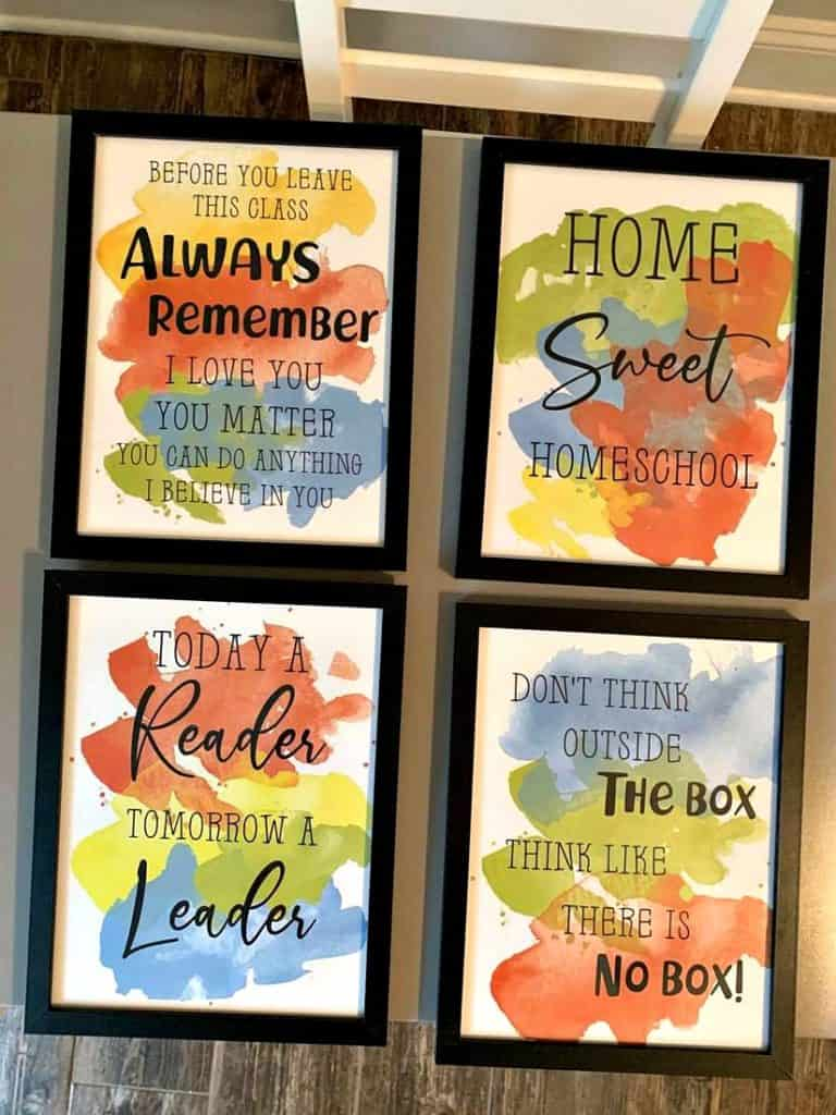 Homeschooling wall art printables with motivational phrases and colorful paint in the background of the words. printables are framed and displayed as decor in a homeschool room
