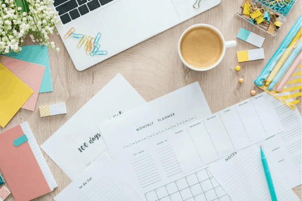 customizable homeschooling planner printables spread out on a desk with colorful desk accessories, laptop and cup of coffee in the background