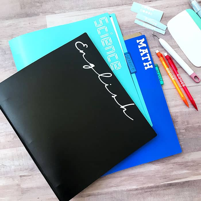 Homeschool folders in black, blue and turquoise neatly labeled by subject on wood background