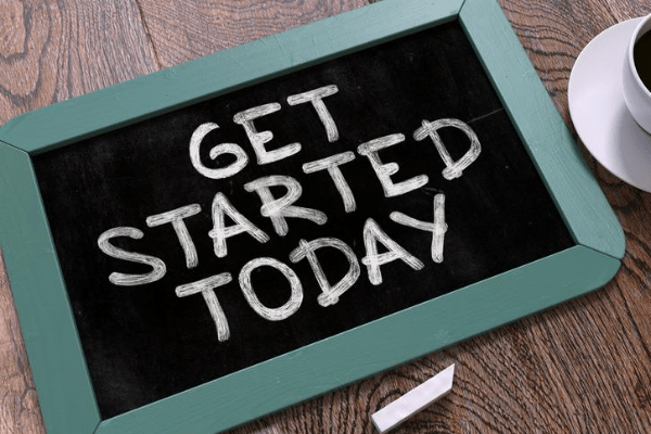 "chalkboard sign with a green wood border that reads ""get started today"" and chalk and cup of coffee in the background"