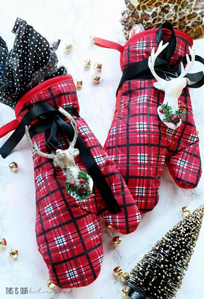 Red and black plaid oven mitt gift idea with colorful printed tissue paper and tied with black ribbon and holiday deer toppers, on marble background with mini Christmas trees