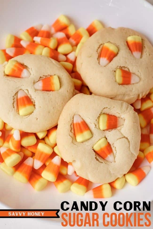 Candy corn cookies in a white bowl filled with candy corns.