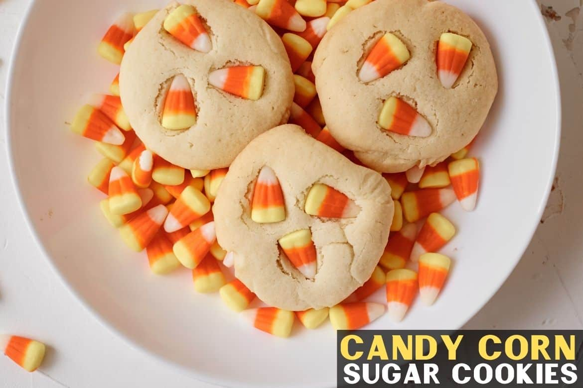 Candy corn sugar cookies in a white bowl with candy corns in bowl.
