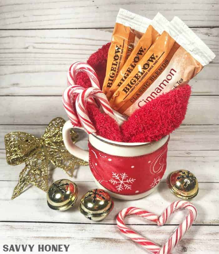 White Christmas mug filled with red cozy socks, tea, and candy corns, red snowflake ribbon wrapped around cup, gold box, gold bells and candy corns in the backgrouns