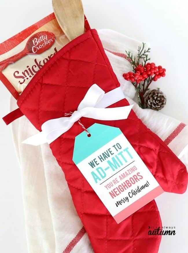 Red Dollar Tree oven mitt filled with cookie mix and wooden mixing spoons, with gift tag and white striped towel in background.
