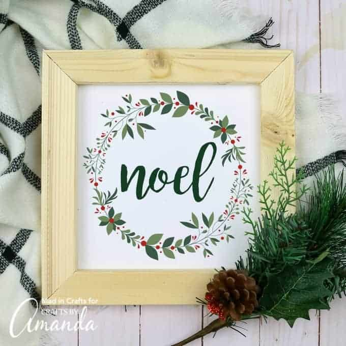 "Wood frame with free Christmas printable that says ""noel"" and has a holiday design, towel and pine branches in the background."
