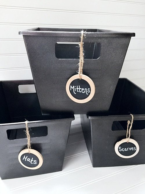 DIY Storage bins painted grey from the dollar tree with tags hanging off front with labels, white background