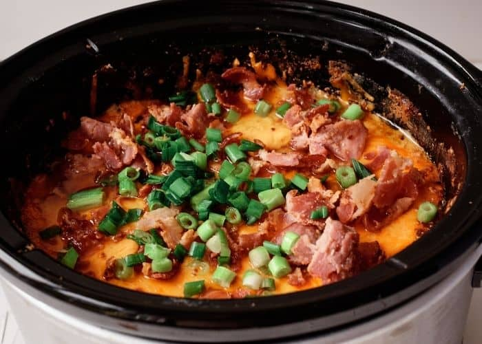 Easy crack chicken in a silver crock-pot with meted cheddar cheese, bacon and green onions on top