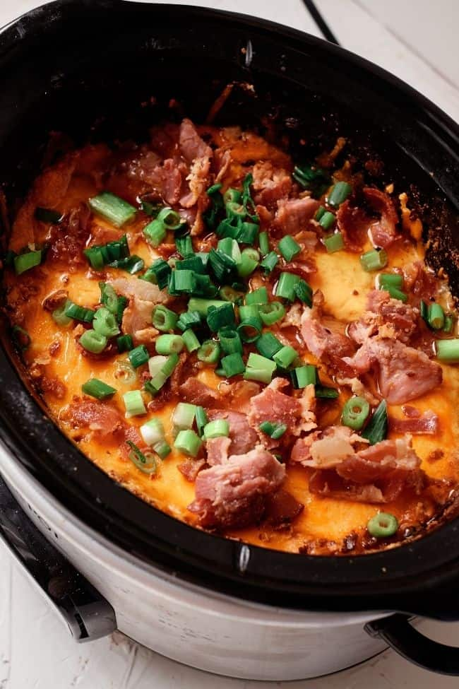 Silver crock pot filled with shredded keto crack chicken and bacon and green onions on top, white background