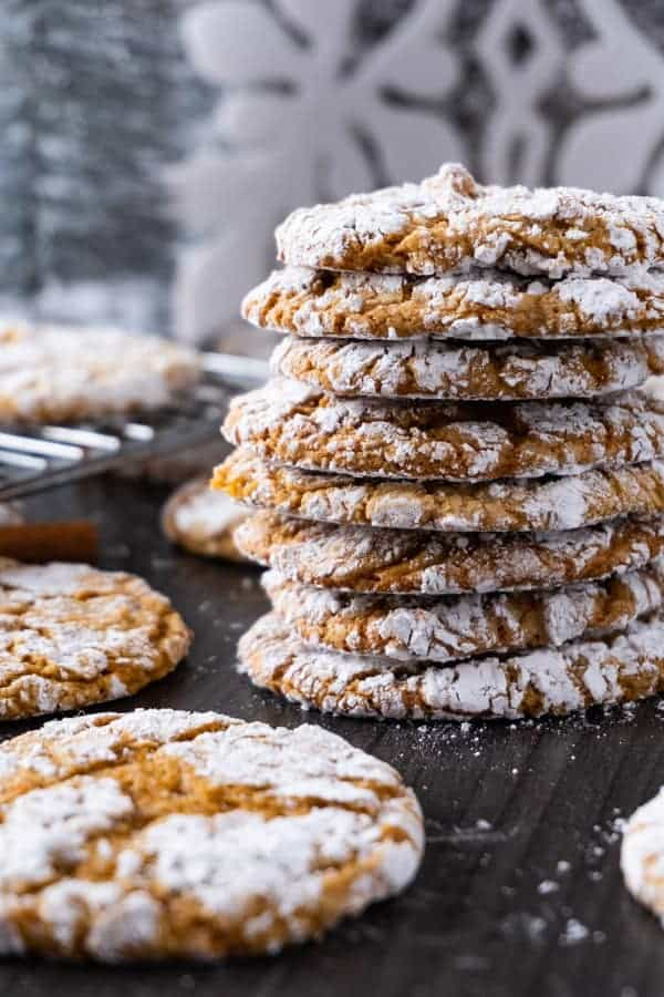 Cookie exchange gingerbread cookies stacked on each other sprinkled with powdered sugar with white and grey background