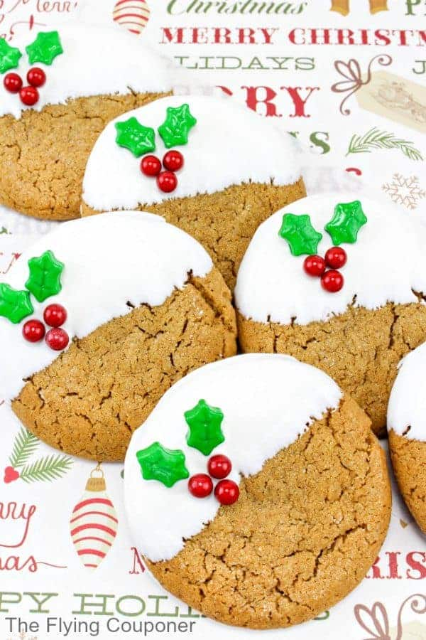 """Gingerbread cookies dipped in chocolate with candy holly on a background that reads """"Merry Christmas"""""""
