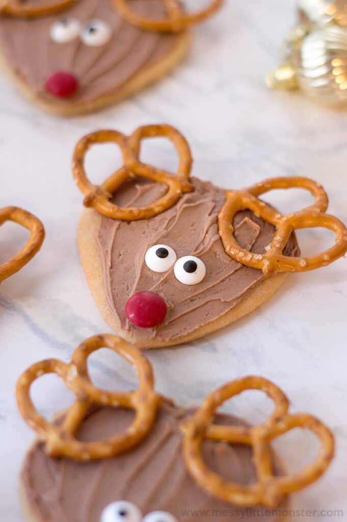 Reindeer Christmas sugar cookies with pretzel antlers and candy eyes and nose on a grey marble background