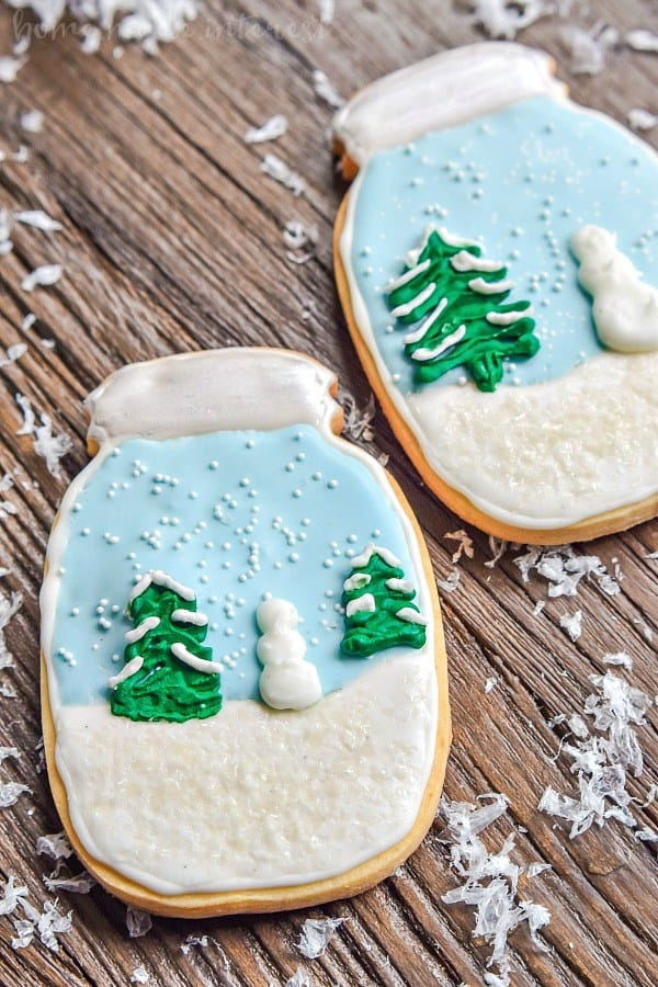 Snow globe cookies on a wood background with fake snow sprinkled around them