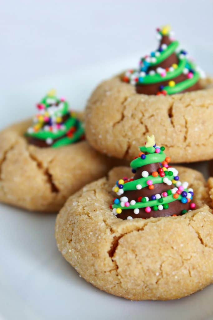 Peanut butter blossom cookies with Hershey Kiss decorated as a Christmas tree with icing and sprinkles on a white background