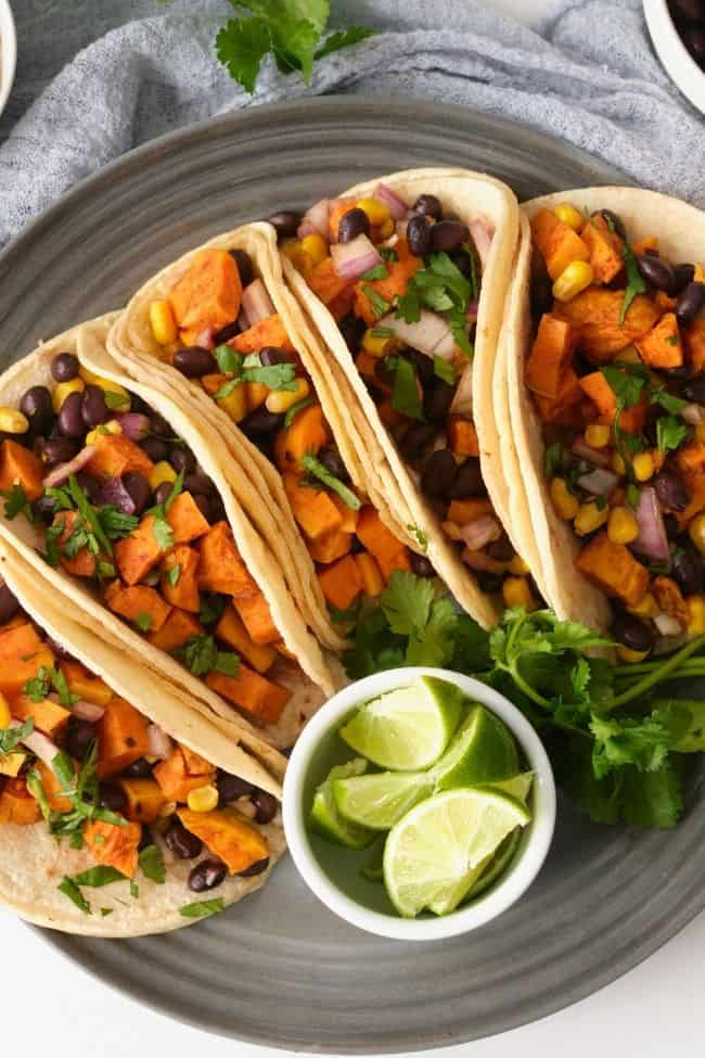 Gluten free sweet potato tacos on a grey plate topped with shredded cilantro, little white bowl on plate with cut up limes, white background