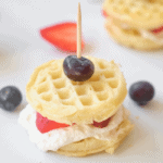 Waffle sandwich idea, two frozen mini Eggo waffles filled with whipped cream and sliced strawberries held with toothpick and blueberry on top, berries scattered on a white background