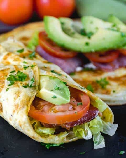 lowcarb breakfast burrito made with egg and stuffed with avocado, bacon, lettuce and tomatoes on a black background