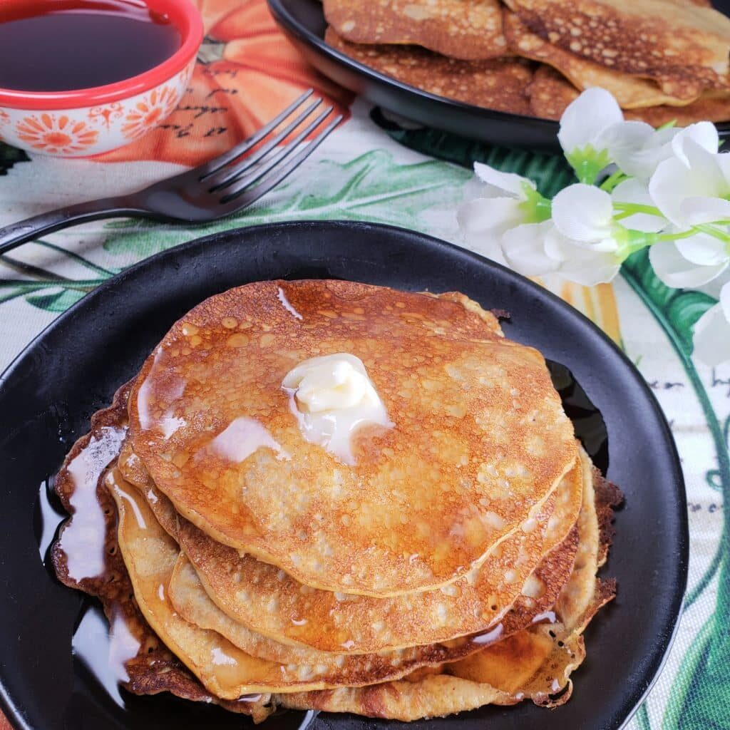 Stack of low carb pumpkin pancakes with syrup and butter on top on a black plate, with colorful table cloth in the background and a bowl of syrup as well as another plate full of pancakes