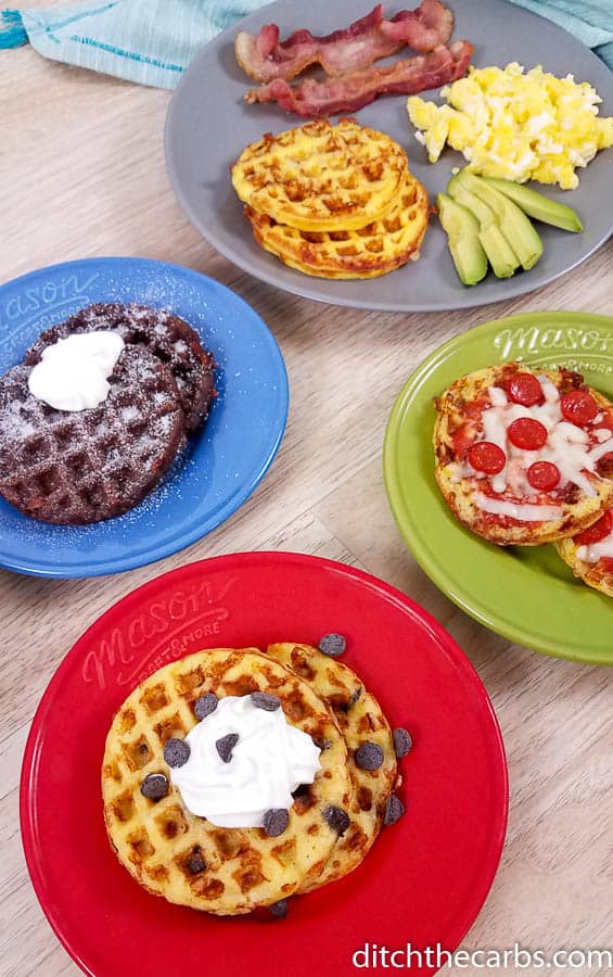 4 types of keto chaffles on colorful plates on a wood background