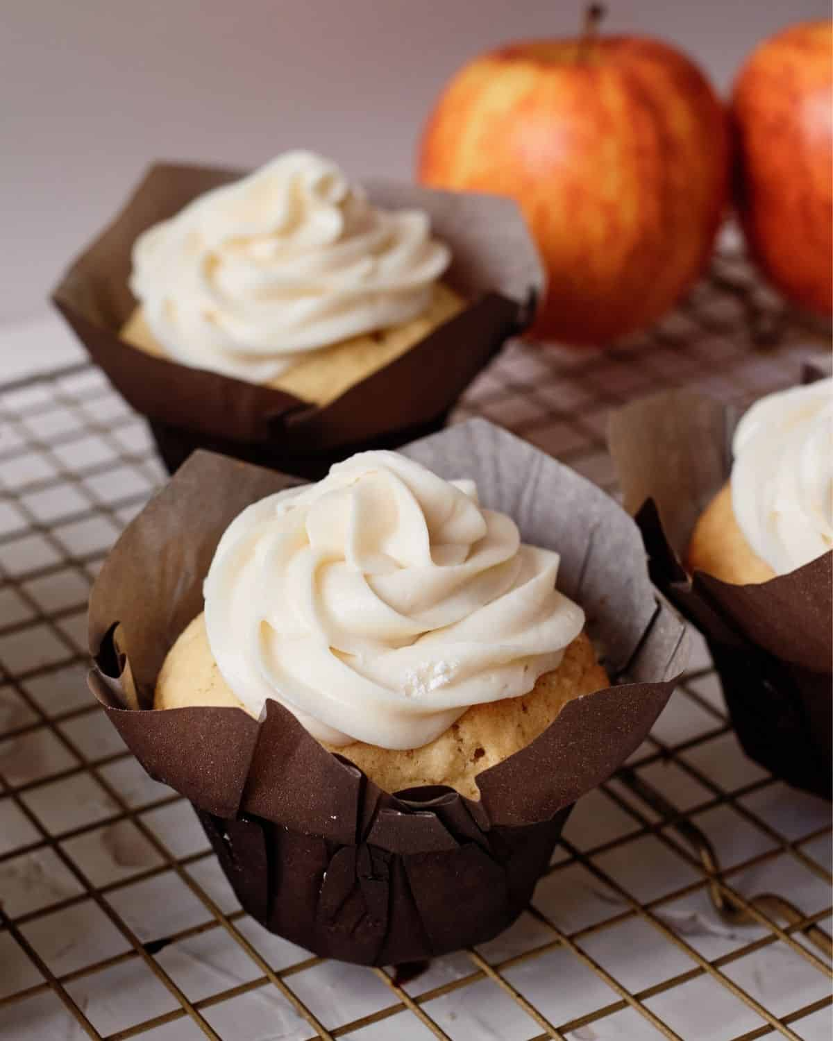 Frosted cupcakes in a dark brown cupcake liner on a baking rack with apples in the background
