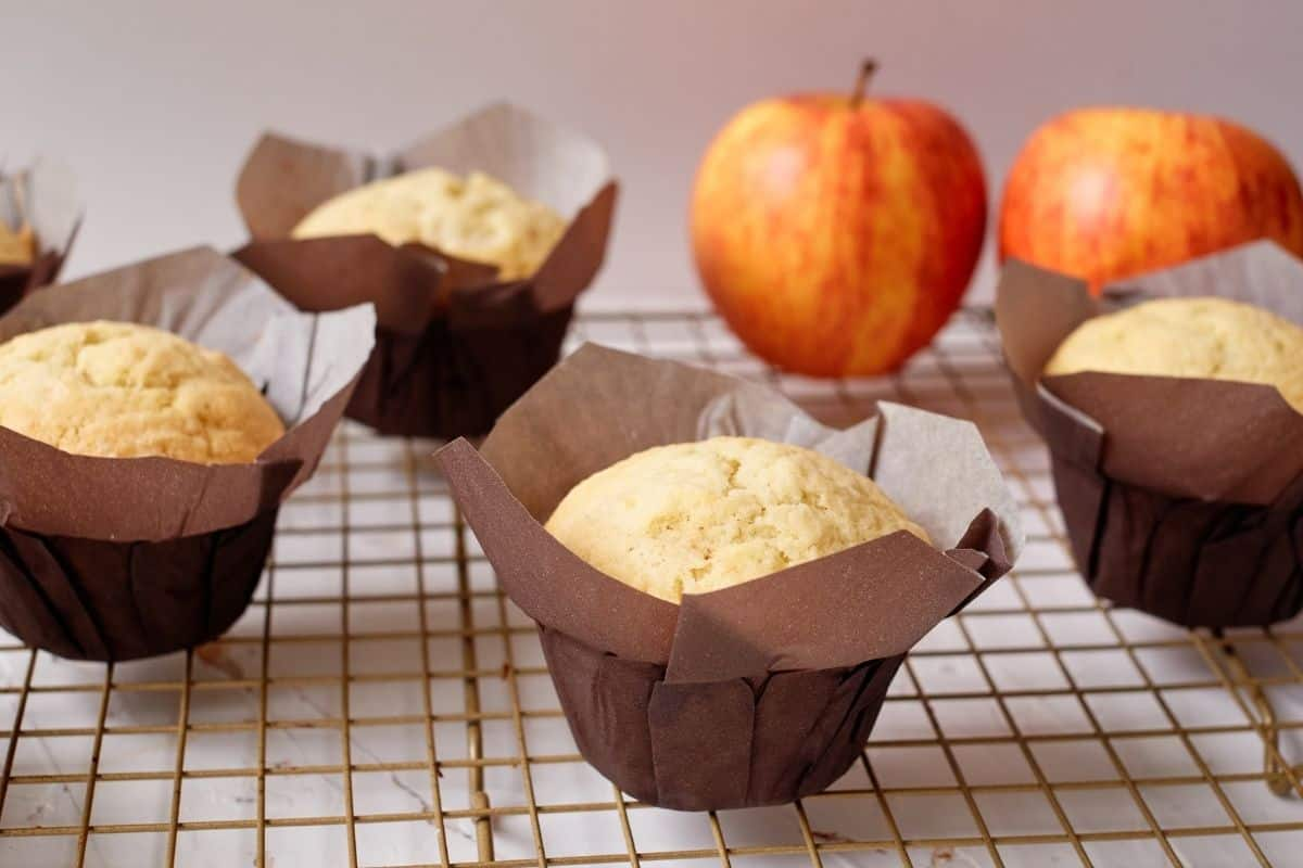 Apple cupcakes without frosting in cupcake liners on a gold cooling rack with fresh apples in the background