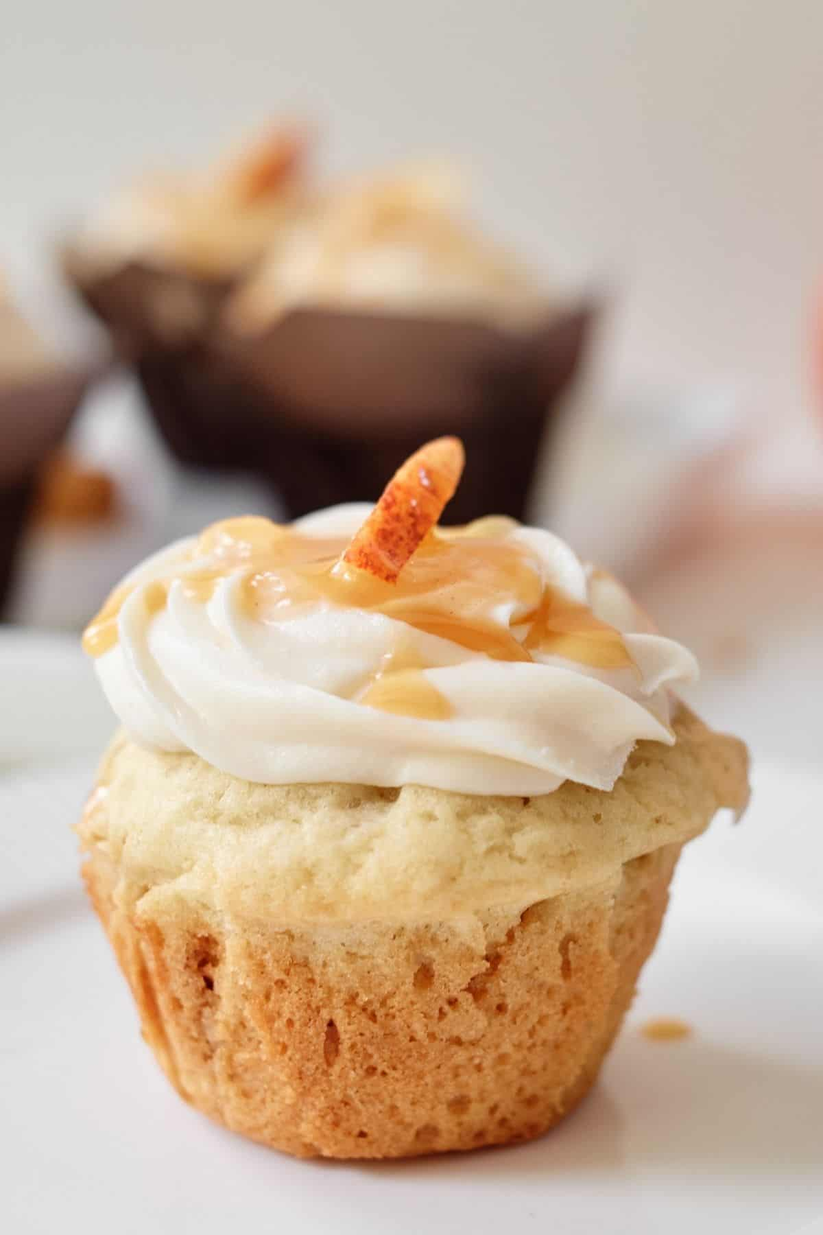 Apple cupcake without cupcake liner topped with caramel frosting and drizzled with caramel sauce and decorated with one apple slice on a white background